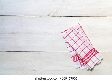 Red kitchen towel on light wood background