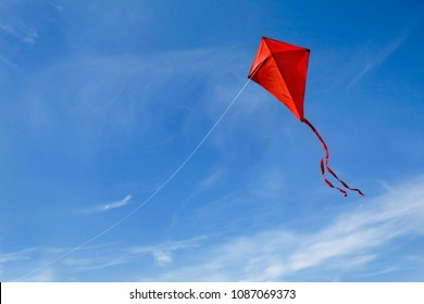 A red kite flying against a blue sky.