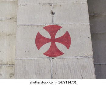 a red knights templar cross painted on a wall in a church