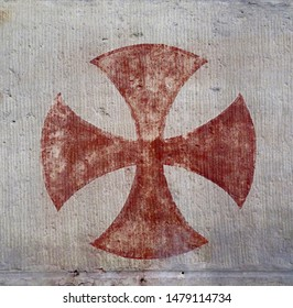 a red knights templar cross painted on a wall in a church, close