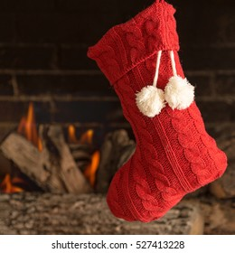 Red knit Christmas stocking hanging over fireplace with room for text