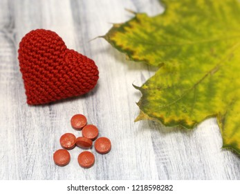 Red knitted heart with pills and maple leaf on wooden table, selective focus. Concept for antidepressants, heart disease, health care, blood pressure, autumn cold and flu, canadian medicine