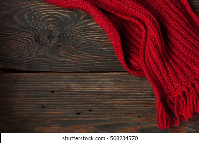 Red Knitted scarf on wooden background, with space for text