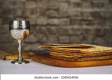 Red kosher wine with a white plate of matzah or matza and a Passover Haggadah on a vintage wood background presented as a Passover seder meal with copy space.