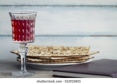 Red kosher wine with a white plate of matzah or matza and a Passover Haggadah on a vintage wood background presented as a Passover seder meal with copy space. Perfect for your Passover design mock up