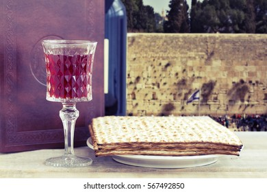 Red kosher wine with a white plate of matzah or matza and a Passover Haggadah on a vintage wood background presented as a Passover seder meal with copy space. Perfect for your Passover design