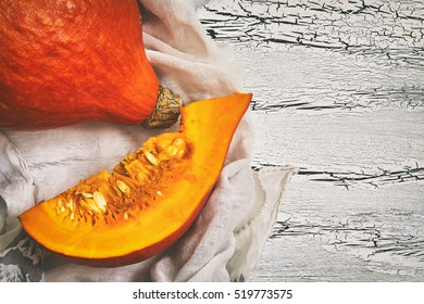 Red kuri squash (Hokkaido pumpkin) on white rustic wooden background. Top view with copy space