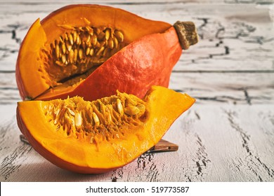 Red kuri squash (Hokkaido pumpkin) on white rustic wooden background