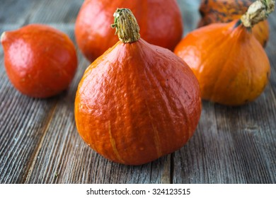 Red kuri squash on wooden background