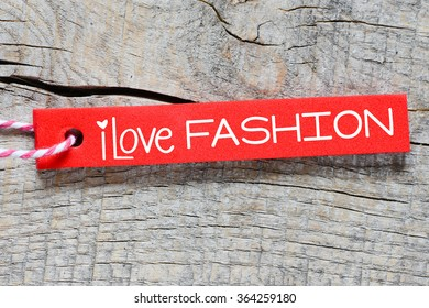 Red label or tag with lettering I love fashion on wooden background