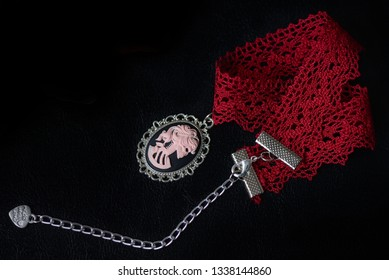Red lace choker with skeleton girl cameo on a dark background close up