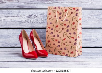 Red lacquered heels and shopping bag. Female leather stilettos and paper bag with spring tulip pattern. Female spring purchase.