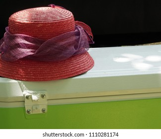 Red lady's hat on top of picnic cooler