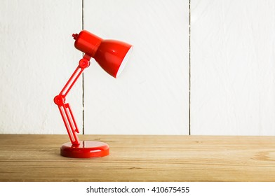Red lamp on wood table over white background