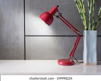 Red lamp with vase of Lucky bamboo on desk in modern room