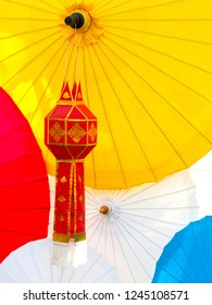 Red Lanna lantern with background of colorful lanna umbrellas.