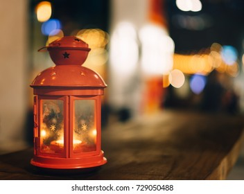 Red lantern candel lamp on wooden table with beautiful abstract blurred light background