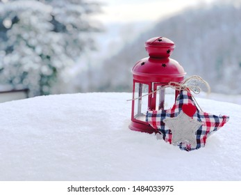 Red lantern and handmade heart on snow across winter landscape. Christmas concept. Copy space