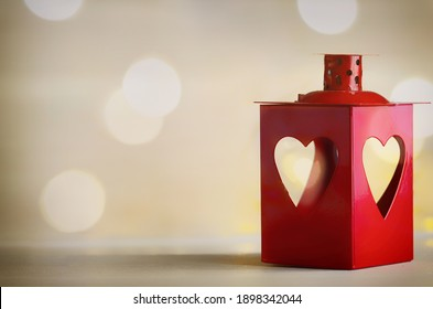 Red lantern with heart on toned background with gold bokeh for Saint Valentines day celebration or love concept.Copy space
