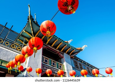 Red lanterns strung across a courtyard between buildings in the Chinatown district in Los Angeles, California, USA