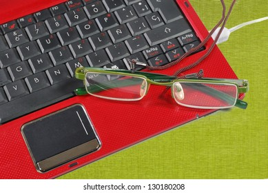 Red laptop and glasses over green tablecloth