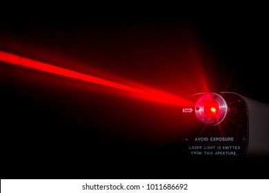 Red laser beam from a lab laser. Warning notice on front. Black background. Beam scatters near aperture.