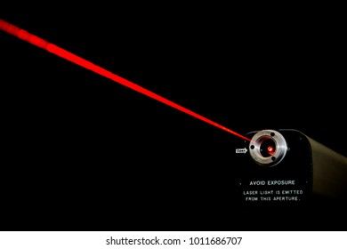 Red laser beam from a lab laser. Warning notice on front. Black background.