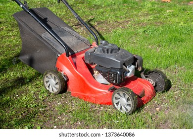 red lawn mower on green home garden