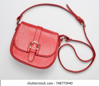 Red leather bag on a white background. Fashionable women's accessories. Top view.