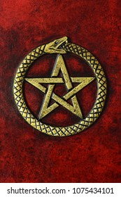 Red leather book with gilded frame, pentagram and metal clasps. Isolated book laying to the table, captured pentagram frontal and close up.