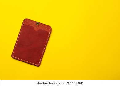 Red leather card holder mock up on yellow background. Sleeve cardholder pocket. Flat lay background. Business concept.