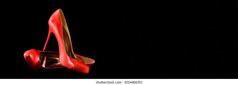 Red Leather High Heel Shoes isolated on Black Backround. Horizontal size banner with copy space.