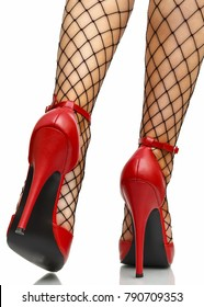 Red leather high heels stilettos with ankle strap and fishnet stockings isolated on white background