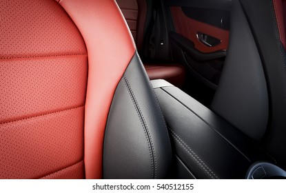 Red leather passenger seat in modern sport car, frontal view, blurred back seats in the background