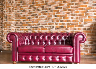 Red leather sofa stands on the brick wall background.