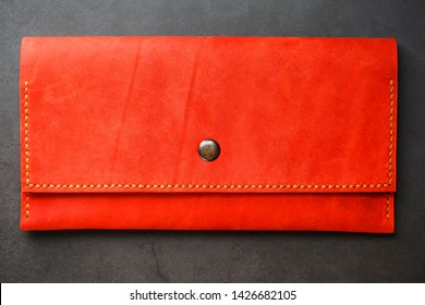 Red leather wallet on a dark background top view. Close-up, purse details, rivet and firmware