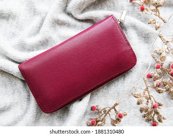 Red  leather wallet on grey knitted background