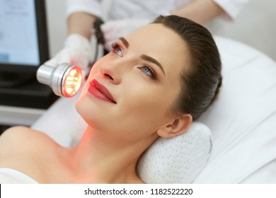 Red Led Light Treatment. Woman Doing Facial Skin Therapy
