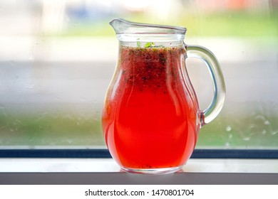 Red lemonade in a decanter on a windowsill against a street background.