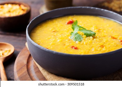 Red lentil Indian soup with flat bread on a wooden background. Masoor dal.