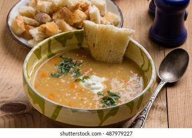 red lentil soup in bowl on rustic table setting