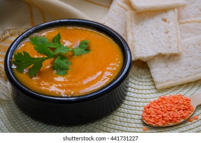 Red lentil soup with cilantro served in black ceramic bowl on wooden background.Healthy eating.