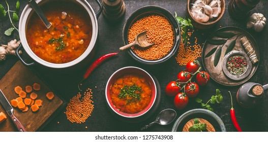 Red lentil soup with cooking ingredients on dark rustic kitchen table background, top view. Healthy vegan food concept. Vegetarian lentil meal dishes. Clean eating.