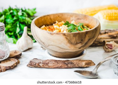 red lentil soup with corn, paprika and herbs in wooden plate, autumn photo of food