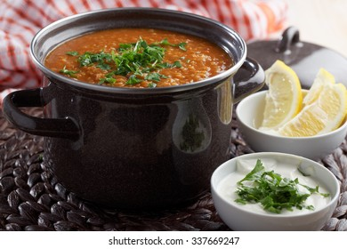 Red lentil soup and Greek yogurt with parsley on a rustic table