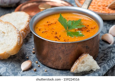 red lentil soup with spices in a copper saucepan, close up, horizontal