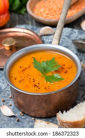 red lentil soup with spices in a copper saucepan, close-up
