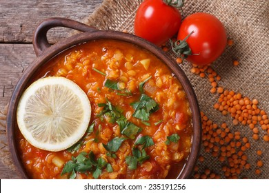 Red lentil soup with tomatoes and lemon close up horizontal. top view