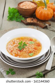 Red lentil soup with vegetables in the plate on the table