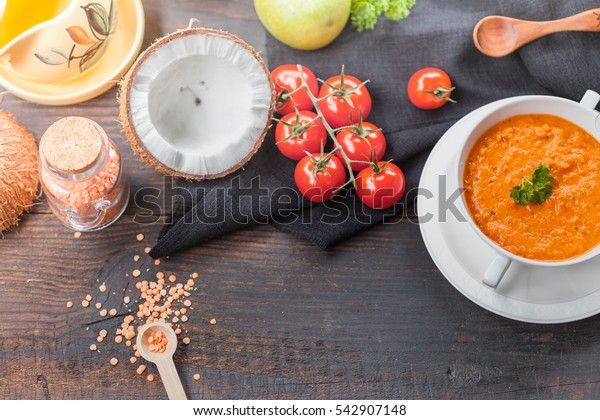 Red lentil and tomato soup in white bowl on old black rustic table, copyspace